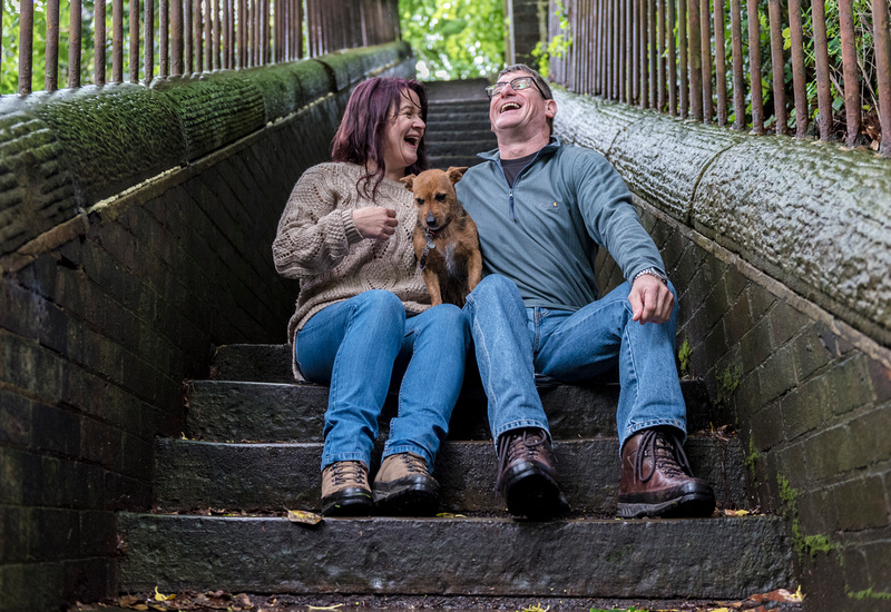 the bride and groom to be on the rickety steps at avenham park with their dog