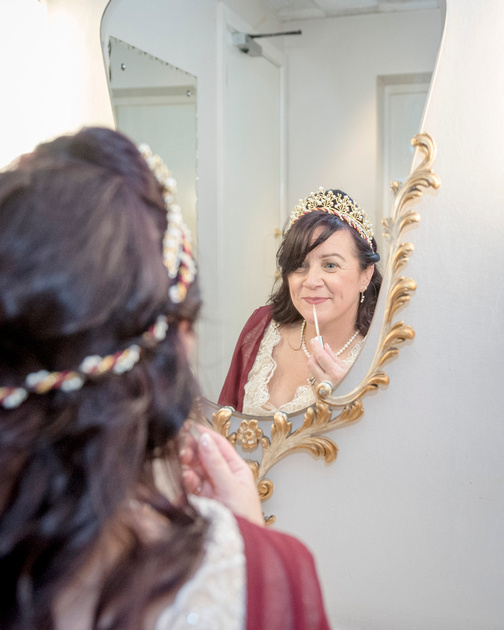 stunning medieval bride applies make up in the powder room at prestons masonic hall