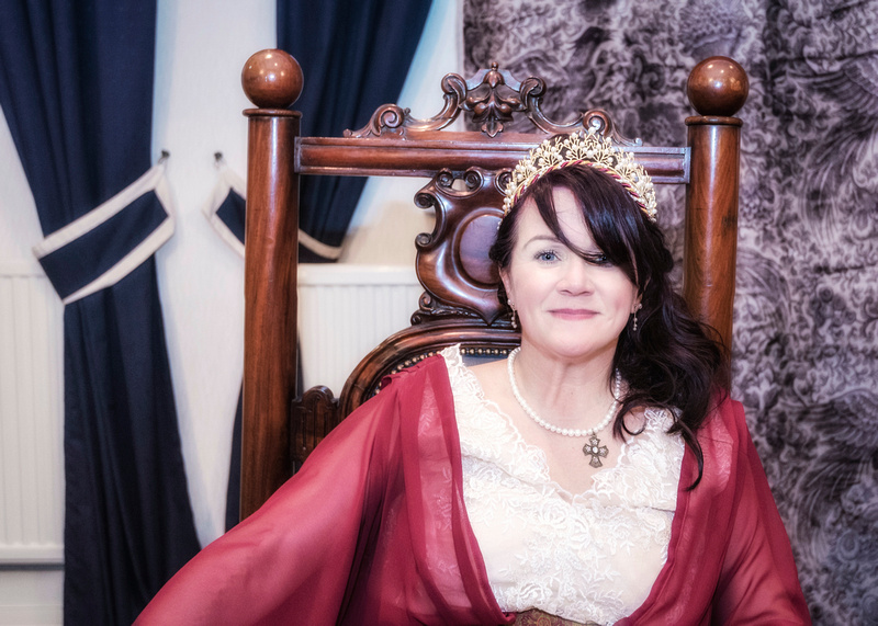 beautiful medieval bride in burgandy and cream wedding dress sat in a stately chair masoni hall preston