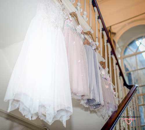 Bridesmaids dresses hanging on staircase in brides house in preparation for wedding at towneley hall burnley lancashire