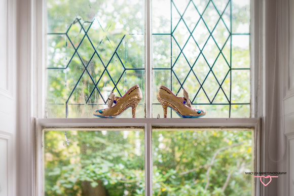 Wedding shoes sat on a bay window sill in the sunlight in preparation for wedding at towneley hall burnley