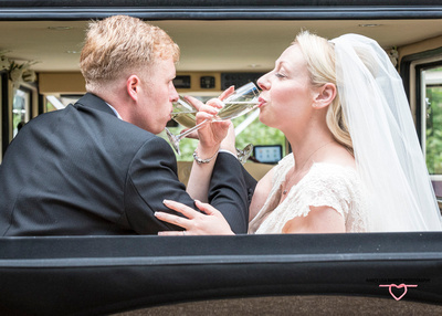 bride and groom link arms and drink champagne at townley hall burnely sat in wedding car