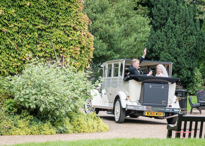 bride and groom waving from wedding car in the distance in the gardens at towneley hall