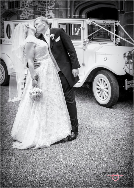 romantic kiss for the bride from groom in front of wedding car at towneley hall burnley