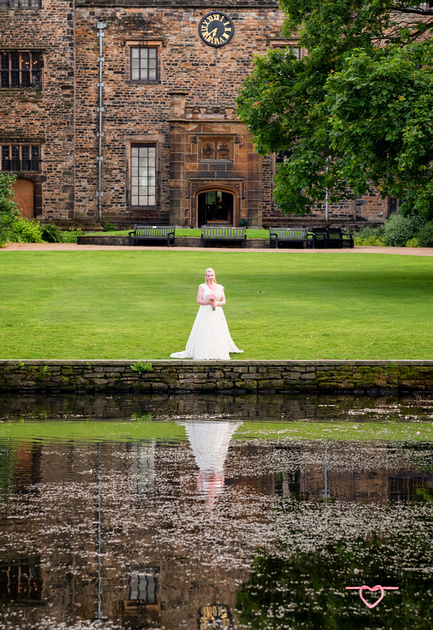 the bride and her reflection in towneley hall gardens with lake and clock burnley