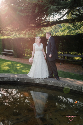 bride and groom in towneley hall gardens with a sun ray right upon them both and reflection