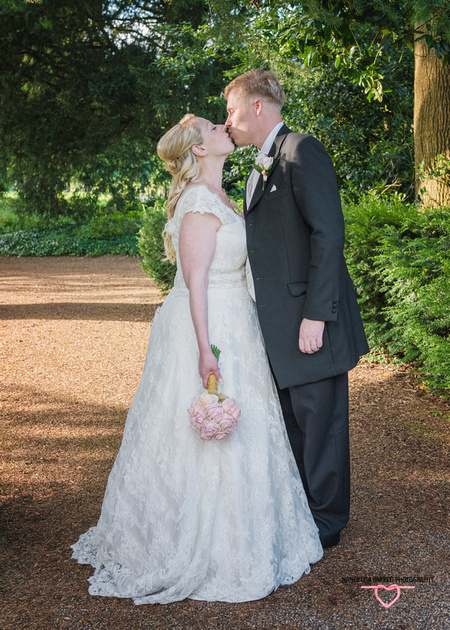 bride and groom romatic kiss in the gardens of towneley hall burnley lancashire