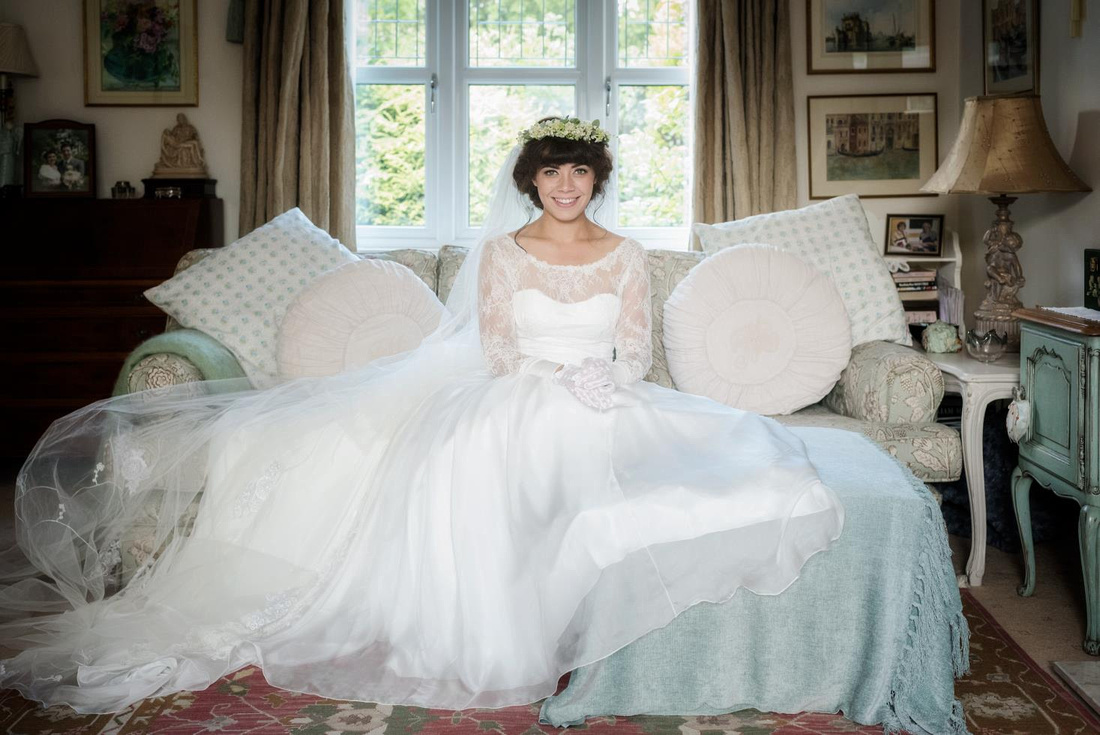 bride sat demurely on a couch in wedding dress veil and tiara in the ribble valley